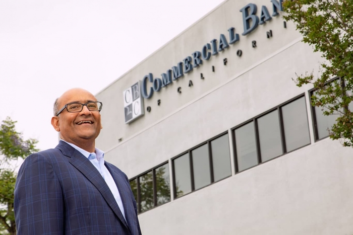 ash patel in front of a building that says Commercial Bank of California